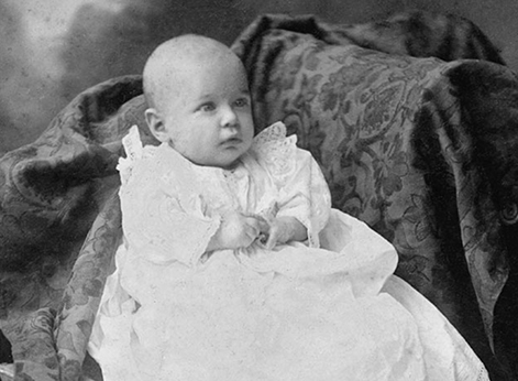 A baby dressed in a fancy, white gown.