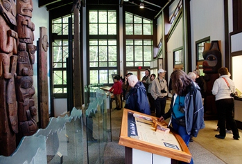 Photo of people viewing totems and museum displays inside Sitka National Historical Park's visitor center