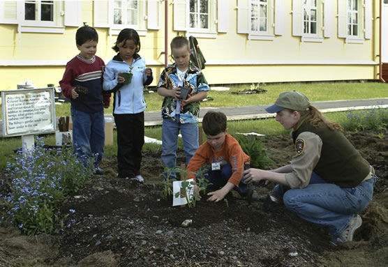 School children learn to garden with the help of a NPS volunteer.