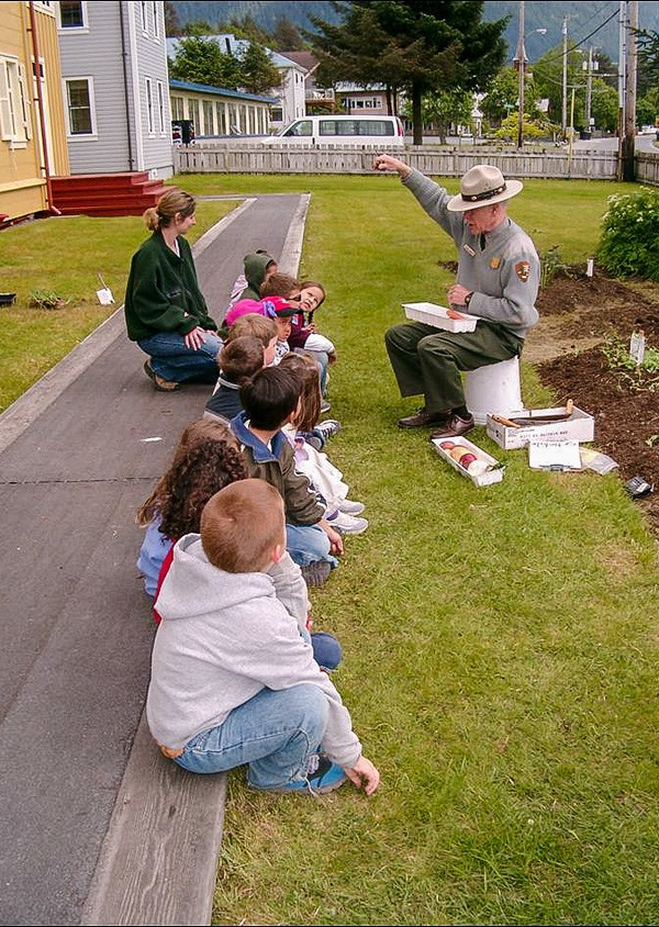 Group of young kids sitting outside attending a Park Ranger program.