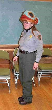 A female Park Ranger in a classroom wearing a formline design costume fish hat.
