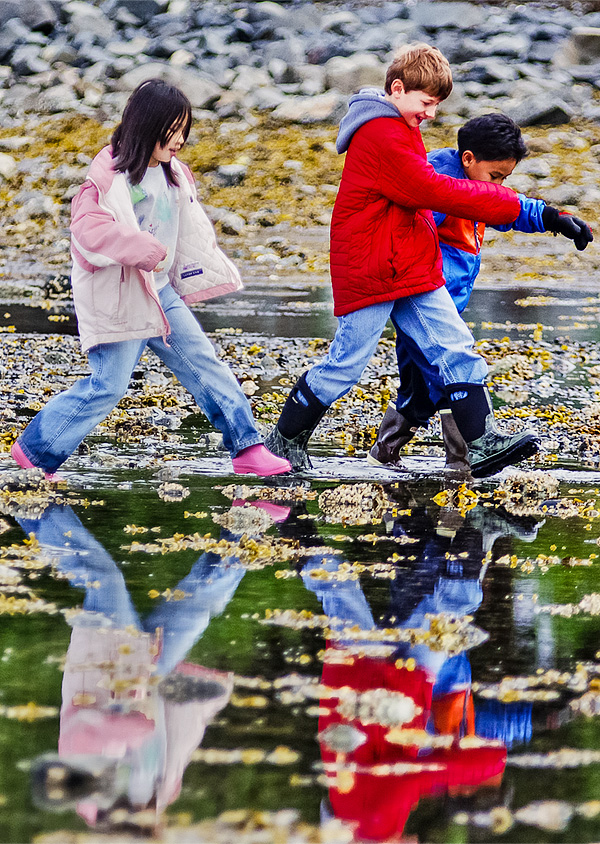Three kids crossing the intertidal lands during low tide.