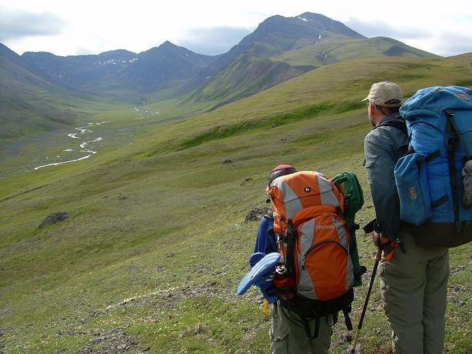 Hikers follow the historic Telaquana Trail in Lake Clark National Park & Preserve, looking out over an alpine meadow with mountains in the background.