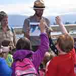 Park Ranger holding picture in front of young students with mountains in the background.