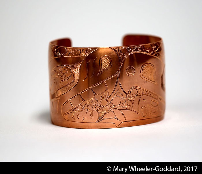 A wide copper cuff bracelet with formline design carvings on the surface.