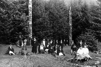 Black and white photograph of a large group of people gathered in a grassy field, with two large totem poles and spruce trees behind them.