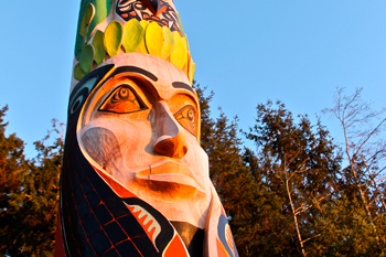 Closeup image of a face carving on Sitka National Historic Park's Centennial Pole with forest and blue sky in the background.