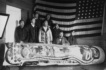 Historic photo of eight Alaska Native men stand behind the Sleeping Man Legend Pole, which is lying on its side.