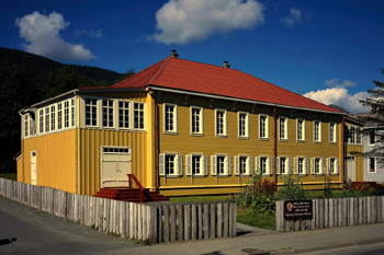 Two-story building painted yellow, with white windows and red roof, surrounded by a wooden picket fence, with blue sky and mountains in the background.