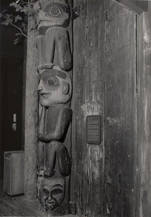 Black and white photograph of the Raven Head Down Pole on display indoors, with a informational plaque hanging next to it.