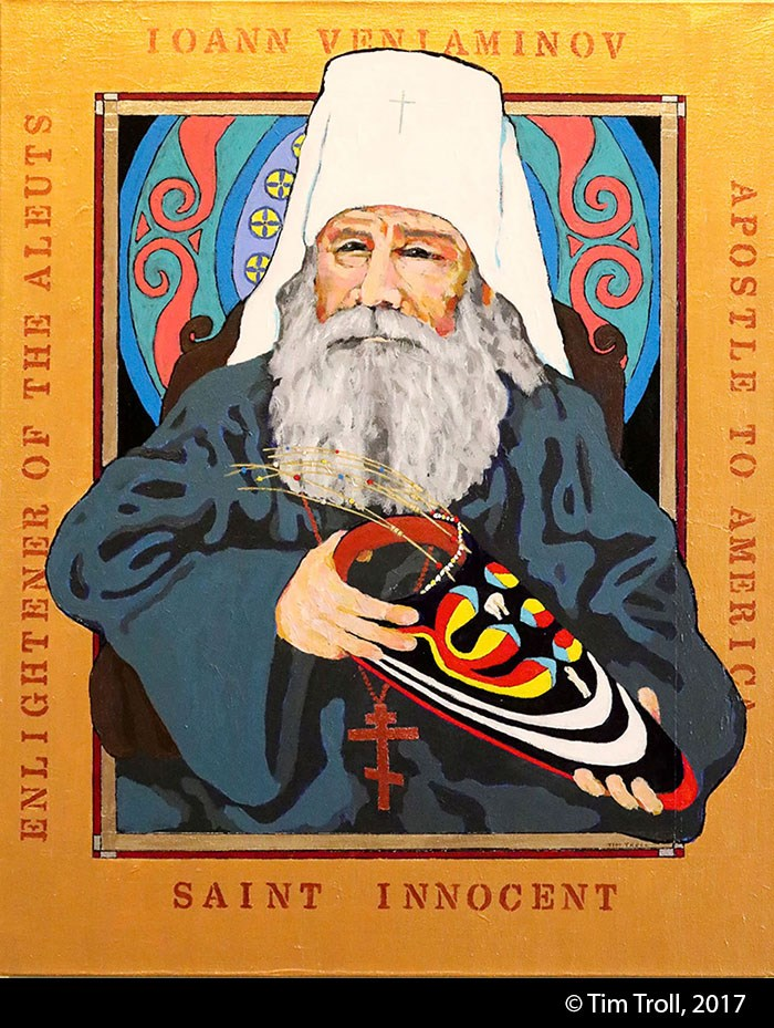 Stylized painting of an elderly white man with long gray beard wearing a tall white orthodox priest's hat, blue robes and red Russian Orthodox cross, holding a brightly painted visor. Gold paint frames the image.