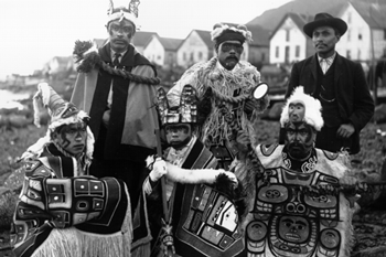 Six Tlingit men, five of whom wear ceremonial garb including headdresses and intricately patterned robes.