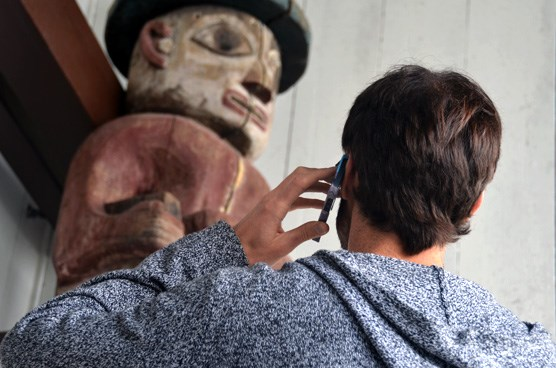 A man looking at a totem pole while listening to his cell phone.