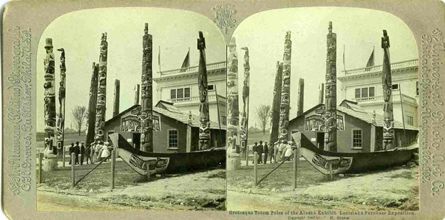Identical side-by-side black and white photographs of the Alaska exhibit at the 1904 World's Fair, with 6 totems poles, a large canoe and a clan house.