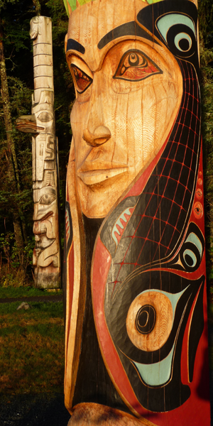 Close-up of the Mother Earth figure on the Centennial Pole with bright red, black and blue paint on her salmon/hair, and a faded totem pole standing in the back left.