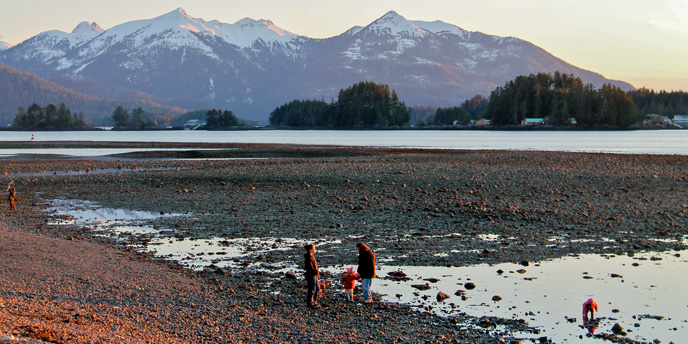 Family with young kids walking along rocky beach with mountains in the background.