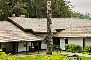 Visitor center building with a totem pole in the foreground.