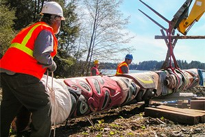 Three people positioning a totem pole with the help of construction equipment.