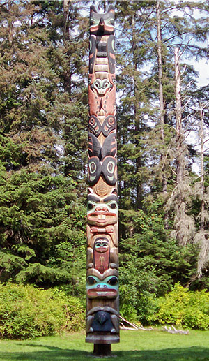Colorful, wood carved totem pole in forest