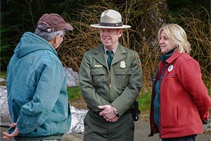 Visitors speaking with a park ranger outside, with forest in the background.