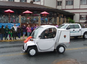 The Park's small two-seat electric vehicle driving down the road during a parade.