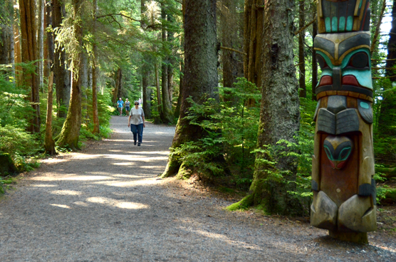 Photo of person walking on gravel path through temperate rainforest with a totem pole in the foreground.