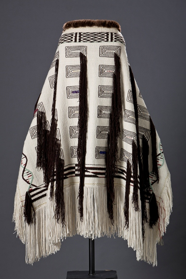 Photo of the black and white, textile DNA Robe, which was woven by Teri Rofkar, on a display stand