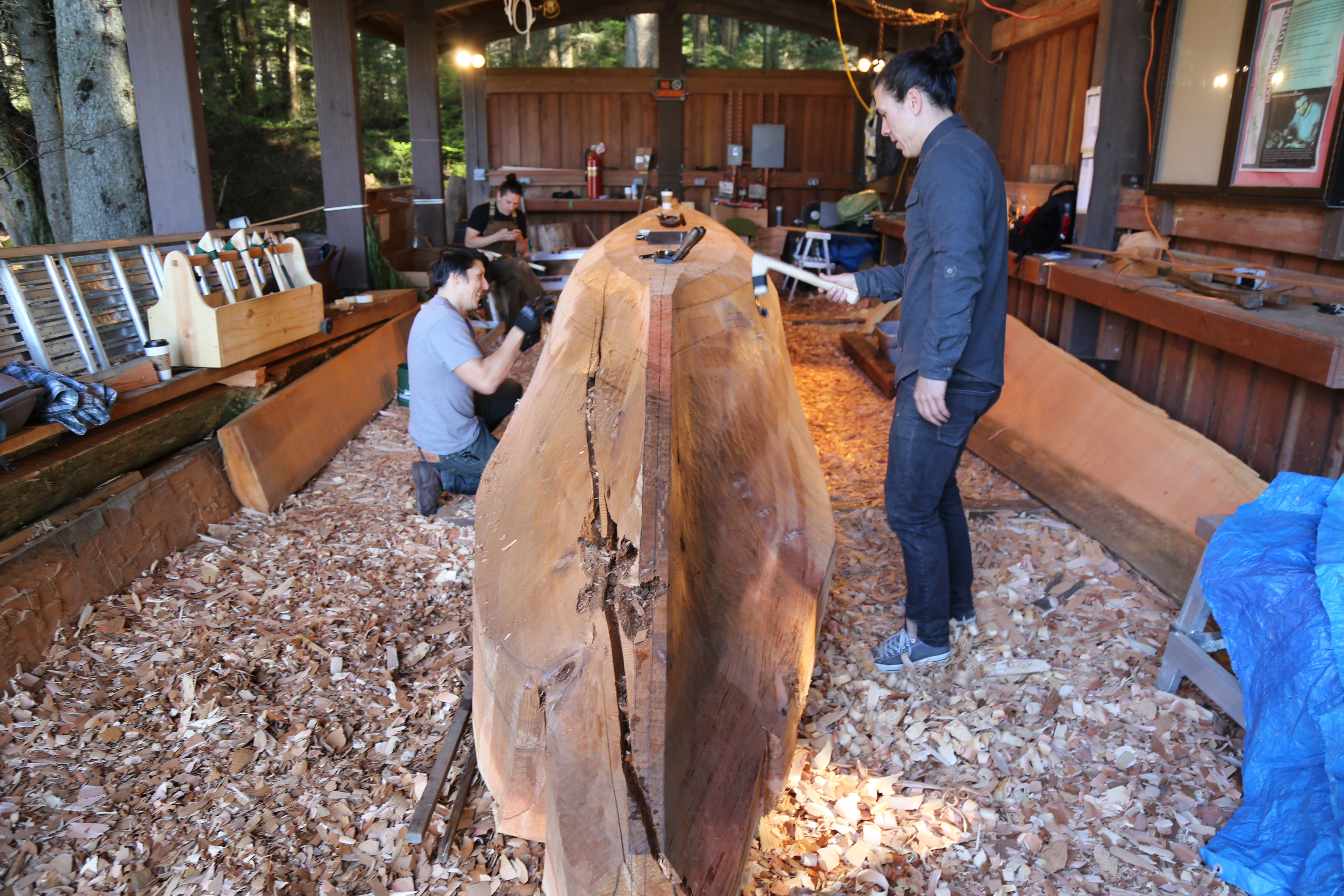 Carvers stand around red cedar log during carving process.