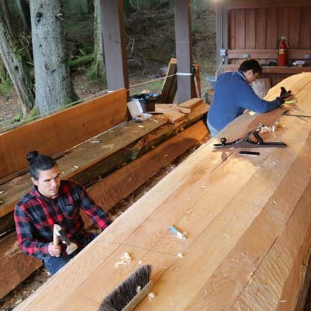 Artists TJ Young and Jerrod Galanin work on the underside of the canoe.