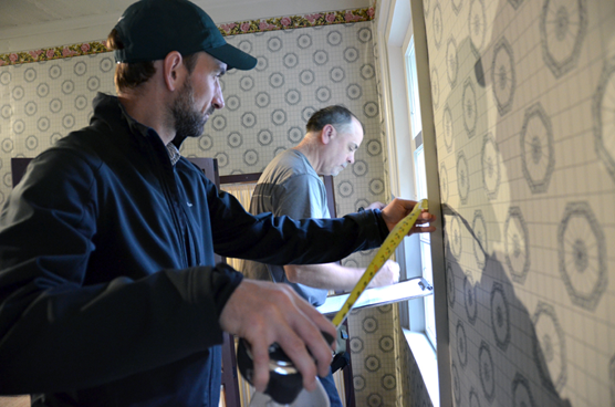 Photo of two engineers measuring and taking notes of room dimensions and attributes in the Russian Bishop's House.