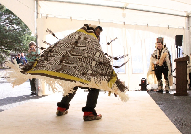 Photo of people viewing a traditional dancer demonstrating an ornate, textile robe.