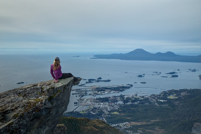 A hiker sits on the edge of the rock at the peak of Verstovia Mountain, overlooking the Sitka Sound.