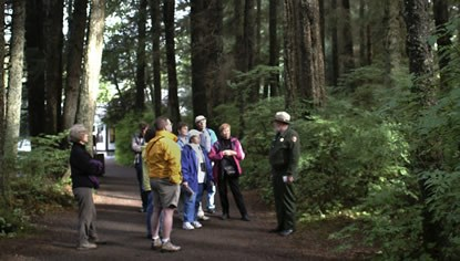 A park ranger leads a group of visitors along the park trail.