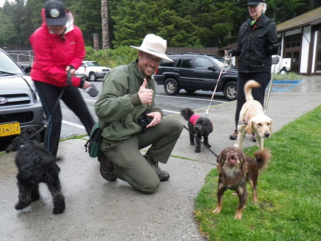 Photo of park ranger kneeling next to four dogs on leashes and their owners.