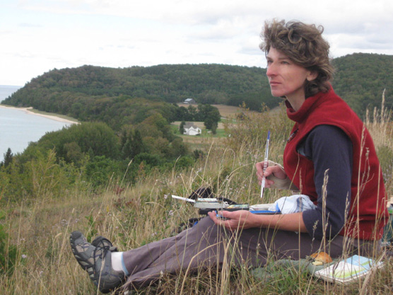 Airtist-in-Residence Kaye Krapohl sketching in Sleeping Bear Dunes National Lakeshore.  Photo courtesy of National Park Service.