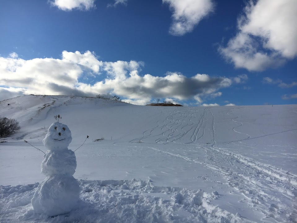 Snowman at base of snow-covered Dune Climb