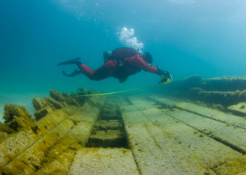 diver measures a shipwreck