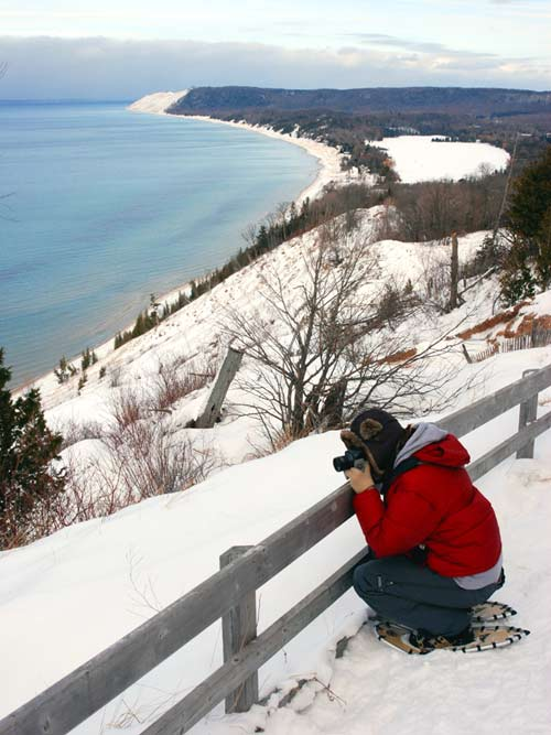 Visitor enjoys the view at the end of the Empire Bluff Trail during a ranger-led snowshoe hike.