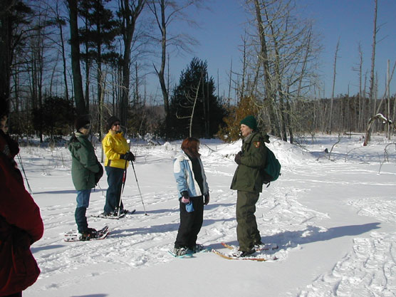 Park Ranger Peg Burman snowshoes with visitors at Tucker Lake in the National Lakeshore.  Photo courtesy of the National Park Service.