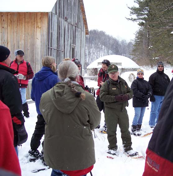 NPS Ranger Bill Herd and snowshoers explore historic farm in Lakeshore.