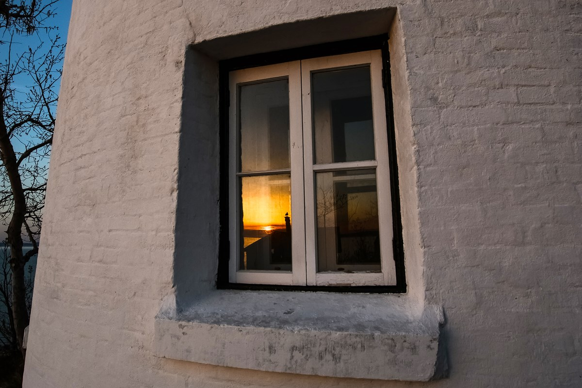 Sunset is captured in the lighthouse window reflection