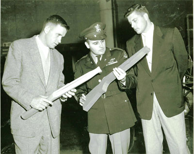 Examining a rough wooden stock blank and a semi-finished shaped stock in WWII