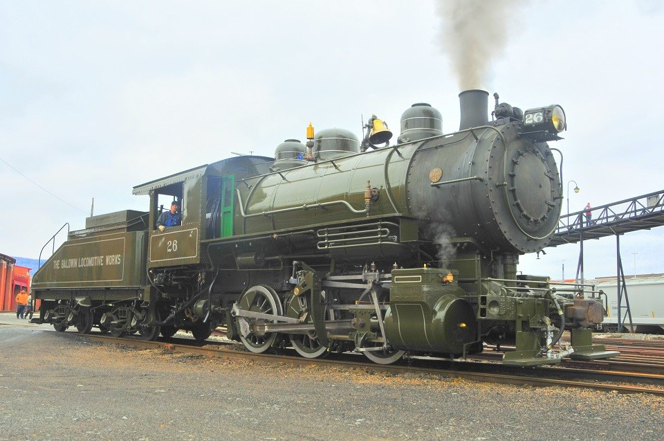 Small switcher locomotive and tender in dark green paint