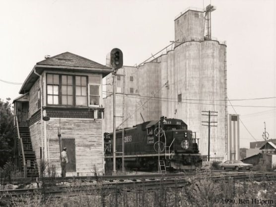 A black and white photo of a diesel-electric locomotive passing a switch tower with grain elevators in the background.