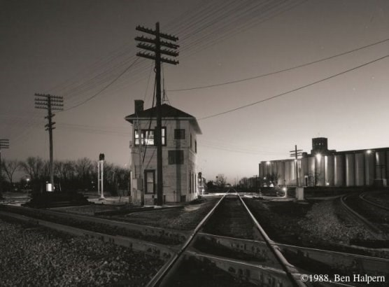 A railroad track diamond - a place where railroad tracks cross each other - withe a switch tower in the background.