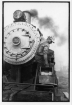A black and white image of a man in work clothes maintains a steam locomotive near it's smokebox.