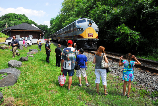 Summer excursionists await trackside to board for a return train ride to Steamtown NHS