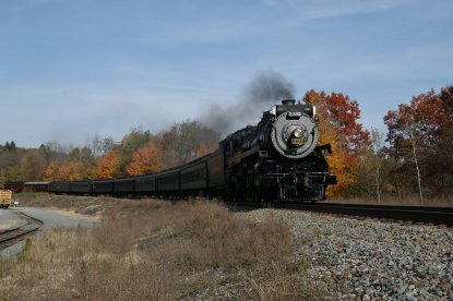 A steam locomotive and passenger excursion train travels along a grassy area in a fall foliage scene.