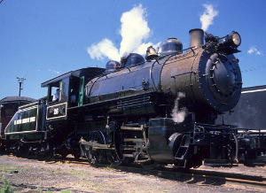 A small, black steam locomotive and tender, with a blue sky and white clouds in background at Steamtown NHS