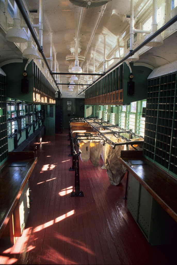 An image of the interior of the L&N #1100 Railway Post Office car, with barred windows along both sides, wooden mail sorting tables and mail holding slots